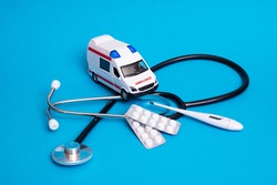 Toy ambulance car and stethoscope on blue background close up