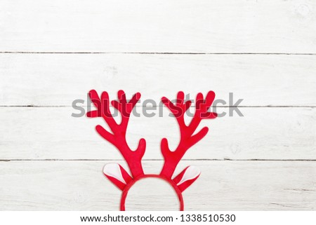 Toy antlers of a deer on white wooden background. Reindeer horns on white wooden texture #1338510530