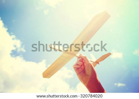 Photo of Toy balsa wood airplane in the sky. Toned filtered Instagram image