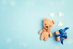 Toy bear and gift box on a blue background with copy space. Greting card concept. Top view, flat lay.