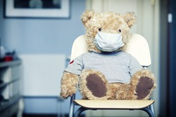 Toy bear in medical mask on face sitting on the chair