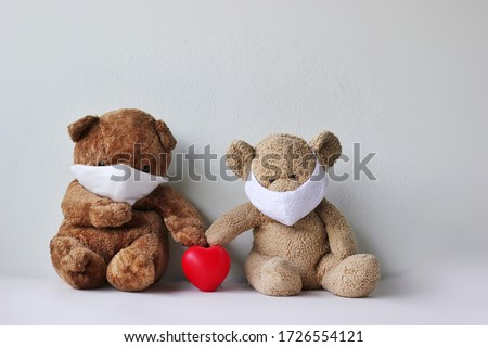 Toy bear in the mask with red heart, Teddy bear wearing face mask protective for spreading of disease virus CoV-2 Coronavirus Disease 2019 quarantine and outbreak alert sign concept.