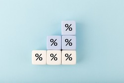 Toy blocks as a ladder with percentage sign on bright pastel blue background. Modern concept of inflation, percent, mortgage or interest rate growth
