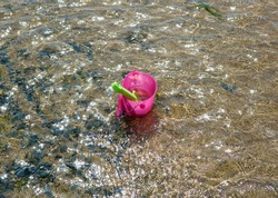 Toy bucket and spade in shallow water
