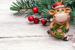 Toy bull in a Santa Claus hat on a white wooden background.Christmas tree branch with red berries in the background. Bull as a symbol of the New year 2021.New Year,Christmas concept