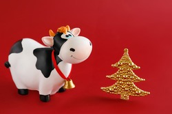 Toy bull with a miniature decorative Christmas tree on a red background. Symbol of the Chinese New year 2021. New year's mood.