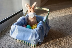 Toy bunny wearing a kid's handmade face mask sitting in an Easter basket with Easter eggs on bedroom carpet in the early morning sun. Stay home and be positive concept.