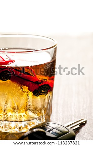 Toy car in a glass of whisky close up with a don't drink and drive concept