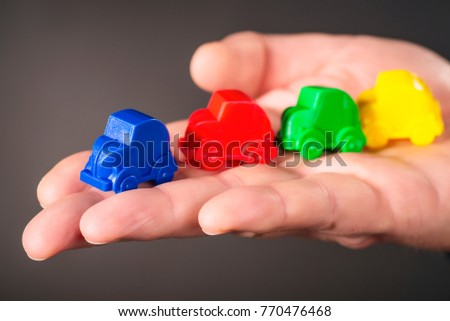 Toy cars in the colors blue, red, green and yellow are carried on a palm. #770476468