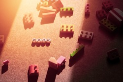 Toy characters lined up with work words, orange sunlight, blurred background.