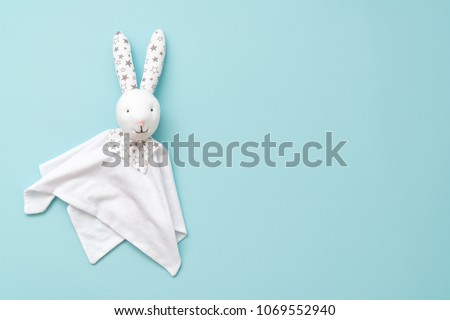 Toy Comforter bunny on a blue background. handy toy for grasping the hands of babies. #1069552940