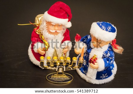 Toy Ded Moroz (Santa Claus) and Snegurochka lighting the Hanukkah candles. In December 2016 Jewish Hanukkah holiday coincides with Christmas and secular New Year.