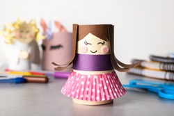 Toy doll made of toilet paper hub on grey table