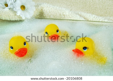 toy ducks and daisies in soap bubbles - stock photo