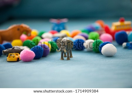 Toy elephant is in focus. In the background, toy cars, small colourful balls, ship toy and helicopter toy is placed randomly. Toys for the child or toddler to play. Child play.
