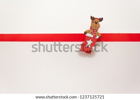 toy elk in a New Year's stocking on a white background. Animation for a happy new year greeting card. Christmas card. White background with red stripe for text.