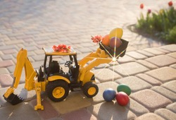 toy excavator - a loader stands on the paving slabs, next to it - colorful Easter eggs. Easter holiday concept for business, construction companies. Sunny spring holiday