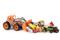 Toy excavator raking a lot of toys from the table. Separate on a white background.