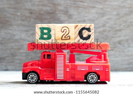 Toy fire ladder truck hold letter block in word b2c (Abbreviation of business to consumer) on wood background