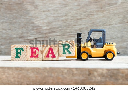 Toy forklift hold block R to complete word fear on wood background #1463085242