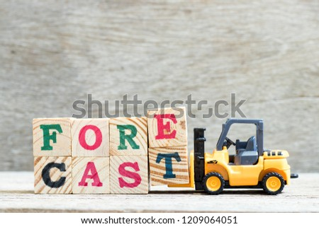 Toy forklift hold letter block e, t to complete word forecast on wood background #1209064051