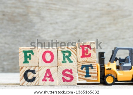 Toy forklift hold letter block e, t to complete word forecast on wood background #1365165632