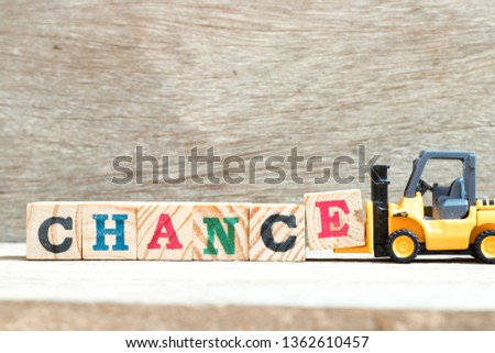 Toy forklift hold letter block E to complete word chance on wood background #1362610457
