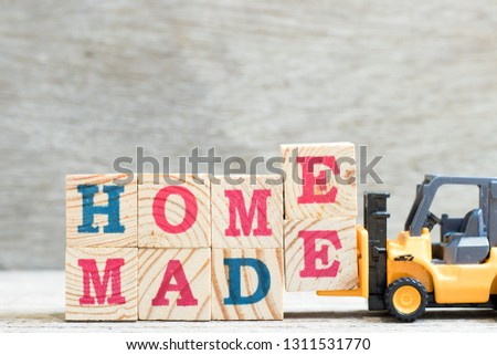 Toy forklift hold letter block e to complete word homemade on wood background