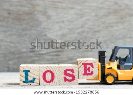 Toy forklift hold letter block e to complete word lose on wood background