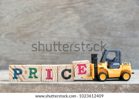 Toy forklift hold letter block E to complete word price on wood background #1023612409