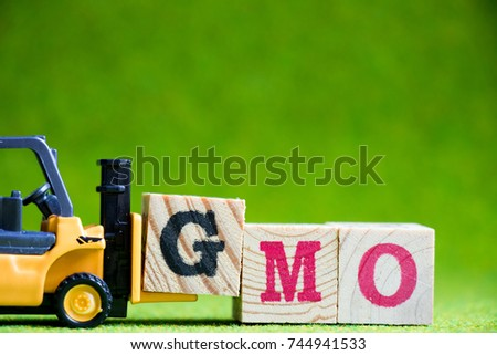 Toy forklift hold letter block G to fulfill word GMO (Abbreviation of Genetically Modified Organisms) on green background #744941533