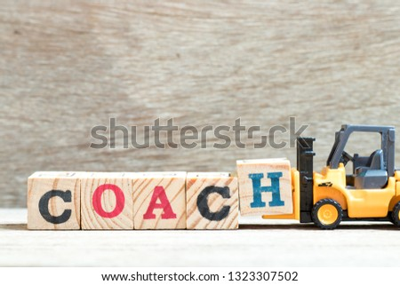 Toy forklift hold letter block h in word coach on wood background #1323307502