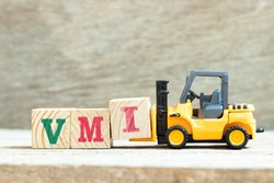 Toy forklift hold letter block I to complete word VMI (abbreviation of vendor managed inventory) on wood background
