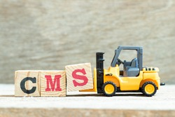 Toy forklift hold letter block S to complete word CMS (Abbreviation of Content management system) on wood background