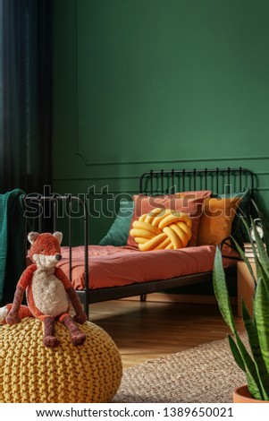 Toy fox sitting on a yellow pouf in a real photo of a kid bedroom with green walls and orange sheets