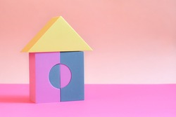 toy house built from building blocks for children on pink background. Colored cubes in shape of house. house made of building blocks. Concept: dream home, happy life, mortgage investment