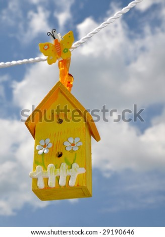 Toy house hanging on the rope against the beautiful sky