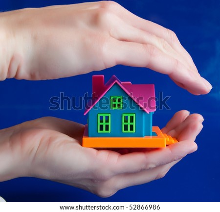 toy house in human hands - a symbol of protection...