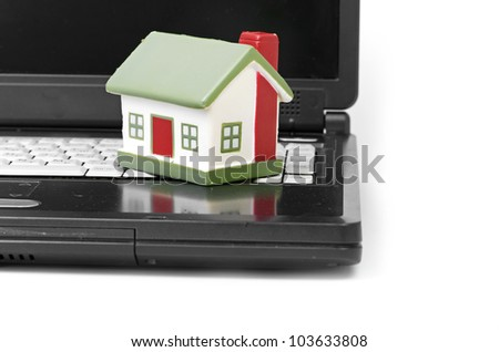 Toy House on laptop isolated on white backgroun