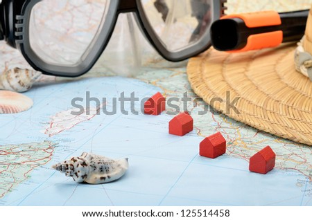 Toy houses on a map with snorkel mask and seashells
