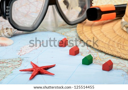 Toy houses on a map with snorkel mask, seashells and starfish