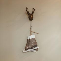 Toy ice skates hang on deer horns hanger on beige wall. Minimalist interior design concept.