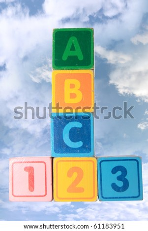 toy letter and number blocks against a cloudy background that spell abc 123 with clipping path