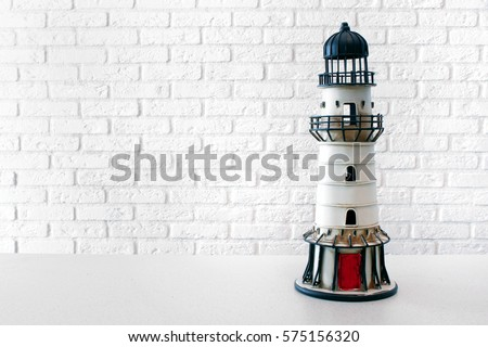 Toy lighthouse on the background of a white brick wall