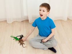 Toy lizards biting boy's finger, he is screaming in pain