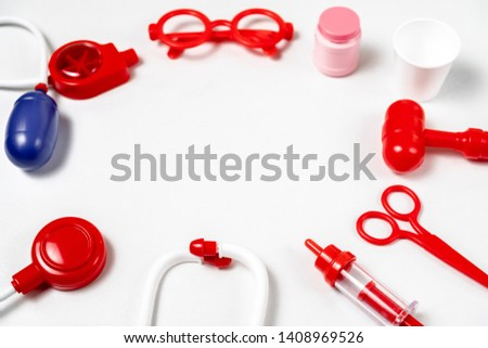 toy medical devices in a semicircle on a white background.  Kids playing profession doctor. Choice of profession #1408969526