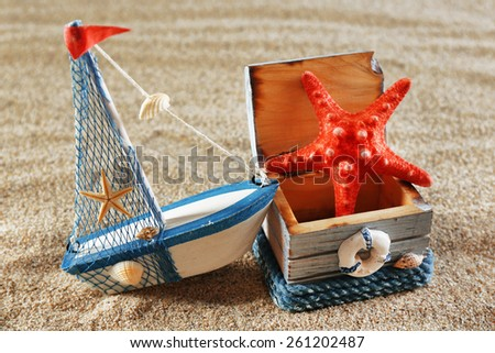 Toy model of ship with wooden box and starfish on sea sand background