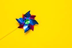 toy multicolor windmill on a yellow background