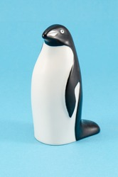 toy penguin figurine on blue background. cute plastic home decoration.