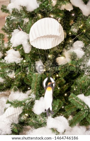 Toy penguin on a parachute. Christmas tree decorations and decorations in the design.